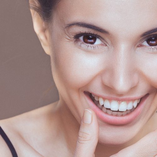 A close-up beauty portrait of a smiling young woman covering her smile with her hand. There are visible wrinkles around her eyes and mouth. The woman has brown eyes, healthy clean skin, natural make-up and dark hair that is swept back from her face. The woman's shoulders are shirtless and visible, and she is isolated on a dark background. Developed from RAW; retouched with special care and attention; small amount of grain added for best final impression; ready made for print and web use;